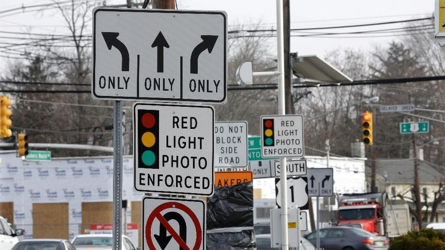 FILE - In a Tuesday, Dec. 16, 2014 file photo, traffic passes a red light photo enforcement sign below a red light camera at the intersection of Route 1 and Franklin Corner Road, in Lawrence Township, N.J. New Jersey legislators recently discontinued the state's red light camera pilot program after five years. The number of red-light cameras nationwide is falling because of opposition from lawmakers and average Joes _ but the use of cameras to catch speeders is slowly rising, potentially signaling a new battleground.   (AP Photo/Mel Evans, File)