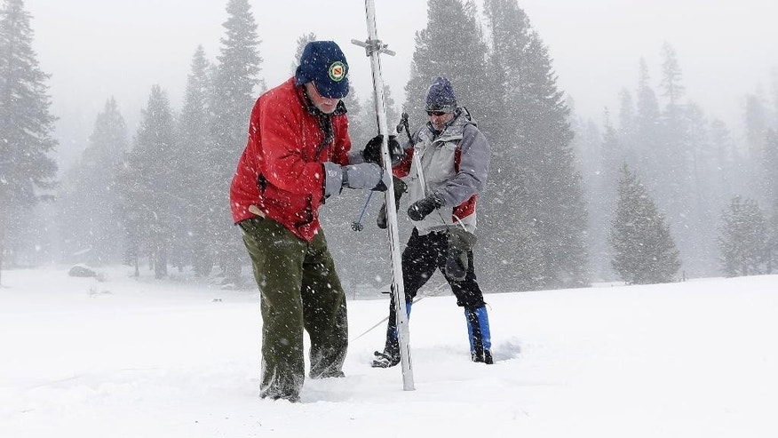 Frank Gehrke, chief of California Cooperative Snow Surveys Program for the Department of Water Resources, left,   pulls the snow depth survey pole from the snow pack as he conducts the first snow survey of the season at Echo Summit, Calif., Tuesday, Dec. 30,  2014. The survey showed the snow pack to to be 21.3  inches deep with a water content of 4.8 inches, which is  33 percent of normal for this site at this time of year.  At right is Dave Schmalenberger, of the Eat Bay Municipal Utility District, who accompanied Gehrke on the survey. (AP Photo/Rich Pedroncelli)