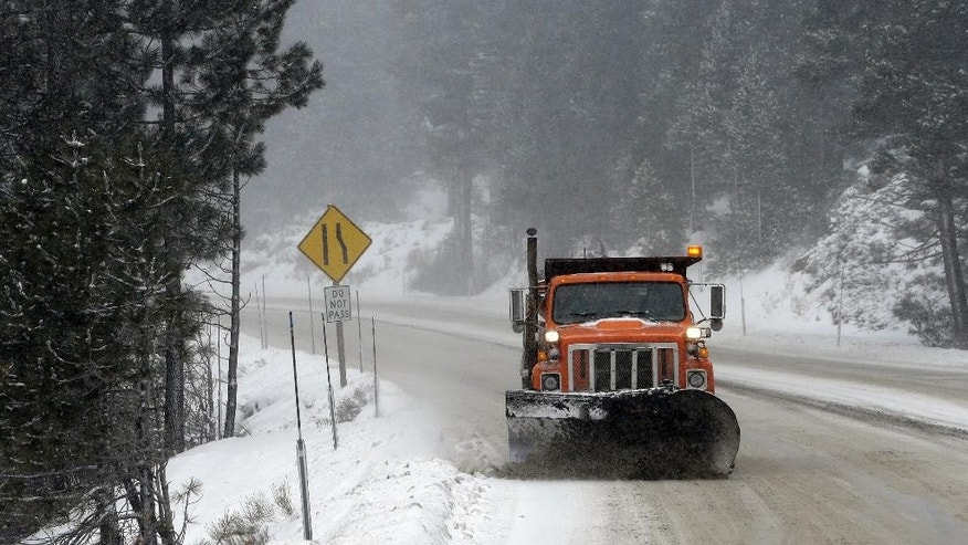 A snow plow clears snow from Highway 50 near Echo Summit, Calif., Tuesday, Dec. 30, 2014. Snow in the Sierra Nevada caused drivers to have to put chains on their vehicles to cross the summit. The California Department Water Resources held the first snow survey of the season near Echo Summit and found the snow pack to to be 21.3  inches deep. The water content of the snow measured Tuesday was about 33 percent of average. (AP Photo/Rich Pedroncelli)