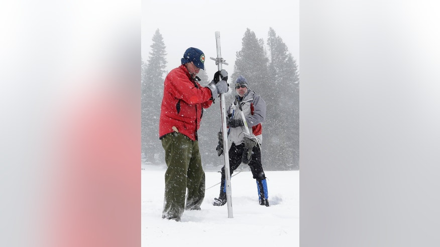 Frank Gehrke, chief of California Cooperative Snow Surveys Program for the Department of Water Resources, left, plunges the snow depth survey pole into the snow as he conducts the first snow survey of the season at Echo Summit, Calif., Tuesday, Dec. 30,  2014. The survey showed the snow pack to to be 21.3  inches deep with a water content of 4.8 inches, which is  33 percent of normal for this site at this time of year.  At right is Dave Schmalenberger, of the Eat Bay Municipal Utility District, who accompanied Gehrke on the survey. (AP Photo/Rich Pedroncelli)
