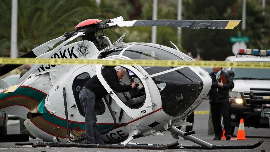 A man takes photos of the wreckage of a Las Vegas police helicopter Wednesday, Dec. 31, 2014, in Las Vegas. Two officers were hospitalized with injuries from the crash. (AP Photo/John Locher)