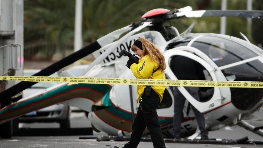 An investigator takes photos of the wreckage of a Las Vegas police helicopter Wednesday, Dec. 31, 2014, in Las Vegas. Two officers were hospitalized with injuries from the crash. (AP Photo/John Locher)