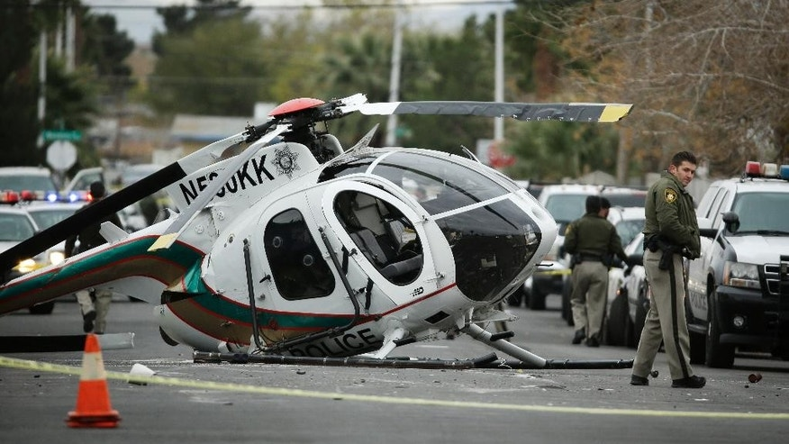 A Las Vegas police officer stands by the wreckage of a Las Vegas police helicopter Wednesday, Dec. 31, 2014, in Las Vegas. Two officers were hospitalized with injuries from the crash. (AP Photo/John Locher)