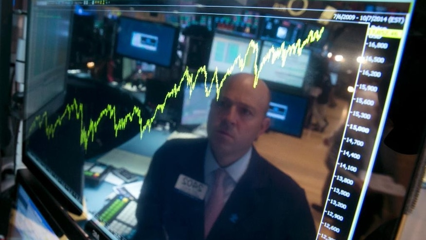 FILE - In this Thursday, July 3, 2014, file photo, specialist Jay Woods is reflected in a screen at his post that shows five years of the Dow Jones industrial average, on the floor of the New York Stock Exchange. Even after a poor start in January and a big wobble in October, the market climbed double digits. The solid gain pushed the bull-run for stocks into its sixth year, the longest since the 1990s. (AP Photo/Richard Drew, File)