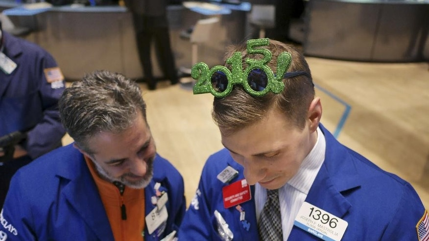 Traders work on the floor at the New York Stock Exchange in New York, Wednesday, Dec. 31, 2014. (AP Photo/Seth Wenig)