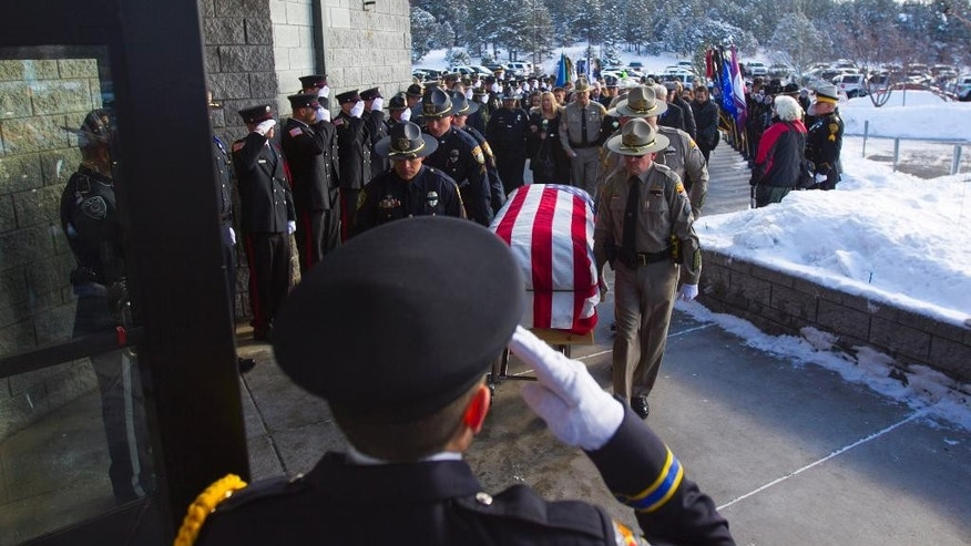 Police officers salute as the coffin of Flagstaff officer Tyler Stewart enters Christ's Church of Flagstaff, Friday, Jan. 2, 2015 in Flagstaff, Ariz. Hundreds gathered Friday for a funeral service honoring Stewart, a Flagstaff police officer fatally shot by a domestic violence suspect. (AP Photo/The Arizona Republic, Patrick Breen)  MARICOPA COUNTY OUT; MAGS OUT; NO SALES