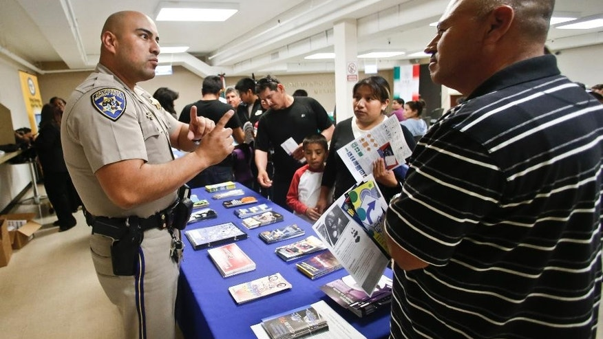 FILE - In this April 23, 2014, file photo, California Highway Patrol officer Armando Garcia explains to immigrants the process of getting a drivers license during an information session at the Mexican Consulate, in San Diego. California is gearing up to start issuing driver's licenses to immigrants in the country illegally in a bid to make the roads safer that could also give more than a million people access to state-issued identification. (AP Photo/Lenny Ignelzi,File)