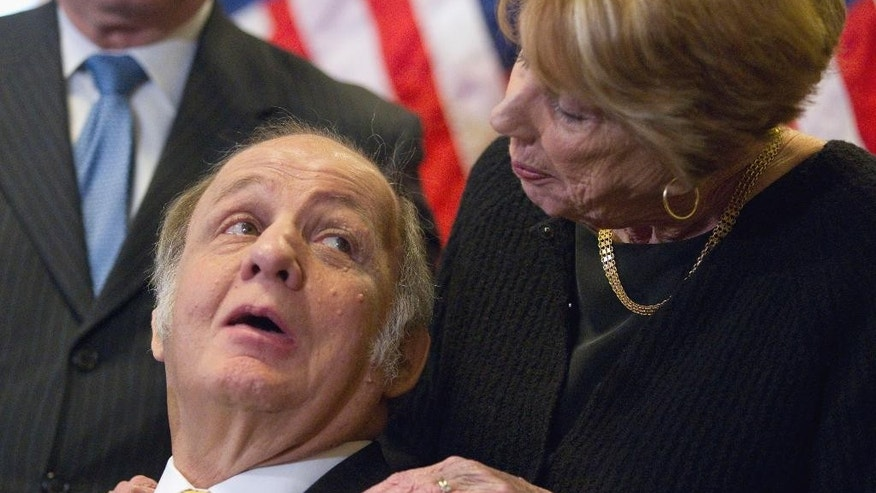 FILE - In this March 30, 2011 file photo, former White House press secretary James Brady, left, who was left paralyzed in the Reagan assassination attempt, looks at his wife Sarah Brady, during a news conference on Capitol Hill in Washington, marking the 30th anniversary of the shooting.  Federal prosecutors say the man who shot President Ronald Reagan and three other people in 1981 won't face new charges in the death last summer of Reagan's former press secretary.  (AP Photo/Evan Vucci, File)