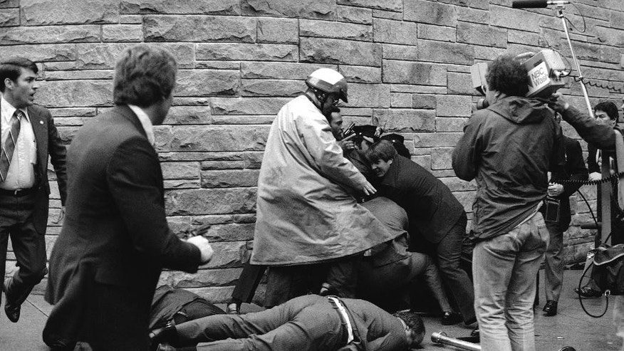 FILE - In this March 30, 1981 file photo, Secret Service agent Timothy J. McCarthy, Washington policeman, Thomas K. Delehanty, and White House press secretary, James Brady, lie wounded on a street outside a Washington hotel after shots were fired at President Reagan.  Federal prosecutors say the man who shot President Ronald Reagan and three other people in 1981 won't face new charges in the death last summer of Reagan's former press secretary.  (AP Photo/Ron Edmonds, File)