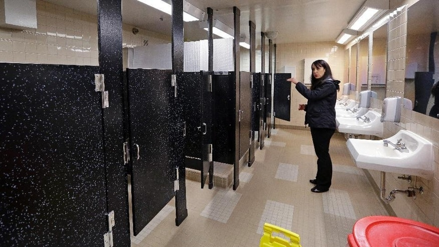 In this photo taken Oct. 17, 2014, Felice Davis, associate superintendent of programs, explains that the height of restroom stall doors allows some privacy but helps to dissuade illicit activity, at the Washington Corrections Center For Women in Gig Harbor, Wash. A 2003 federal law was meant to put a stop to sexual assault in the nation's prisons, jails and juvenile detention centers and more than $110 million in state and federal taxpayer money has been spent to help states tackle the problem. By last fall, every state was supposed to have dozens of new standards in place, ranging from increased training of staff about sex abuse policies to procedures meant to help inmates safely report attacks. (AP Photo/Elaine Thompson)
