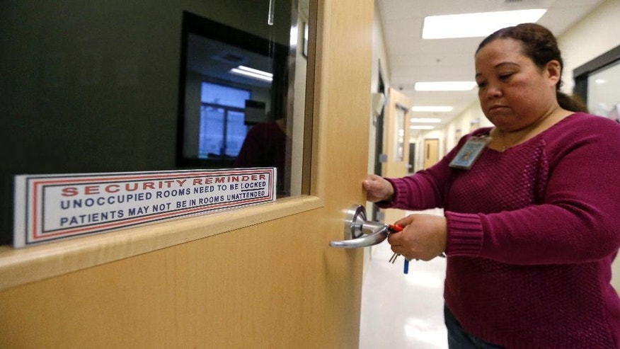 In this photo taken Oct. 17, 2014, a staff member unlocks a door that is marked with reminders that it must be locked when not occupied and that offenders are not to be left alone in the room, at the Washington Corrections Center For Women in Gig Harbor, Wash. A 2003 federal law was meant to put a stop to sexual assault in the nation's prisons, jails and juvenile detention centers and more than $110 million in state and federal taxpayer money has been spent to help states tackle the problem. By last fall, every state was supposed to have dozens of new standards in place, ranging from increased training of staff about sex abuse policies to procedures meant to help inmates safely report attacks. (AP Photo/Elaine Thompson)
