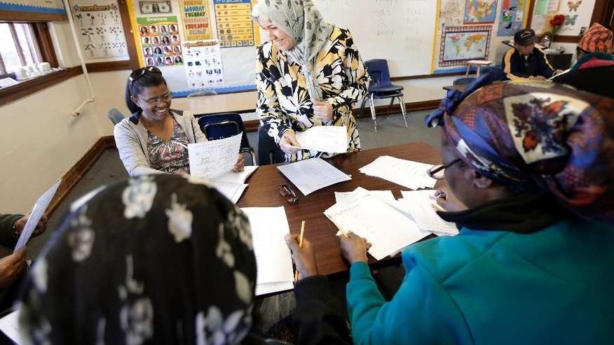 Fatin Jasmin Naser Hussein, standing, of Iraq talks with Maria Figueroa of the Dominican Republic, left, and other classmates as they complete some work in a English as a second language class at the Alta Vista Learning Center, Tuesday, Dec. 16, 2014, in Abilene, Texas. Texas has led the nation in refugee resettlements over the last four years and continues to attract others who move to the state on their own.  (AP Photo/Tony Gutierrez)