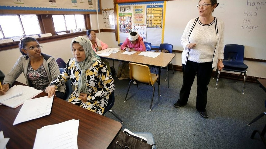 Teacher Teresa Price gives instructions as Maria Figueroa, left front of the Dominican Republic, Fatin Jasmin Naser Hussein, center front of Iraq, Padma Bhujel, left rear, and Pabi Maya Bhujel, both of Bhutan, take notes in a english as a second language class at the Alta Vista Learning Center, Tuesday, Dec. 16, 2014, in Abilene, Texas. Texas has led the nation in refugee resettlements over the last four years and continues to attract others who move to the state on their own.  (AP Photo/Tony Gutierrez)