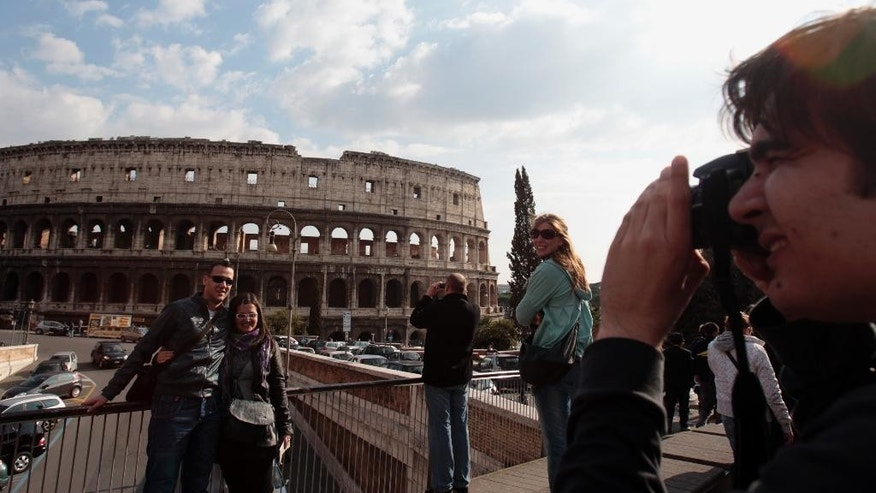 FILE - In this Tuesday, March 22, 2011 file photo, tourists take pictures in front of Rome's ancient Colosseum. A strong U.S. dollar is making world travel cheaper for Americans in 2015. (AP Photo/Gregorio Borgia, File)