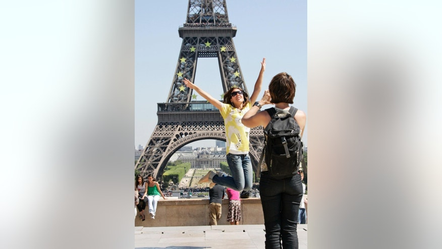 FILE - In this July 22, 2008 file photo, tourists take pictures in front of the Eiffel tower, in Paris. A strong U.S. dollar is making world travel cheaper for Americans in 2015. (AP Photo/Francois Mori, File)