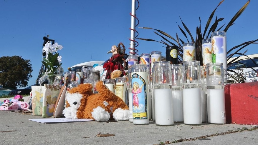 A small memorial rises on a sidewalk near the location of a dumpster in which the body of three-week-old Eliza Delacruz was found, Monday, Jan. 5, 2015, in Imperial Beach, Calif. The child's parents and uncle were shot and wounded in Long Beach, Calif. and baby's body was found Sunday. Detectives trying to determine who abducted the infant after shooting her parents and uncle at a Long Beach home are asking for the public's help.    (AP Photo/Lenny Ignelzi)