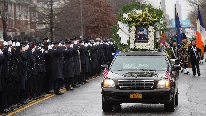 CORRECTS VEHICLE IS NOT A HEARSE  - The vehicle leading the funeral procession of New York Police Department Officer Wenjian Liu, seen in photo, passes along the funeral route as police officers salute, Sunday, Jan. 4, 2015, in the Brooklyn borough of New York. Liu and his partner, officer Rafael Ramos, were killed Dec. 20 as they sat in their patrol car on a Brooklyn street. The shooter, Ismaaiyl Brinsley, later killed himself. (AP Photo/John Minchillo)