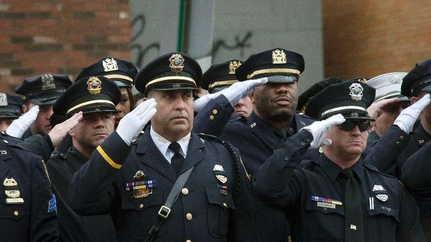 Police officers salute along the procession route during the funeral of New York Police Department Officer Wenjian Liu, Sunday, Jan. 4, 2015, in the Brooklyn borough of New York. Liu and his partner, officer Rafael Ramos, were killed Dec. 20 as they sat in their patrol car on a Brooklyn street. The shooter, Ismaaiyl Brinsley, later killed himself. (AP Photo/John Minchillo)