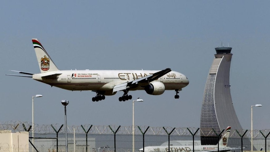 FILE - In this May 4, 2014 file photo, an Etihad Airways plane prepares to land at the Abu Dhabi airport in the United Arab Emirates. Hundreds of air travelers landed in San Francisco Saturday evening, Jan. 3, 2015, safe but irritated after a 28-hour Etihad overseas flight they say included 12 hours on a tarmac at the Abu Dhabi airport without food or accurate flight information. (AP Photo/Kamran Jebreili, File)