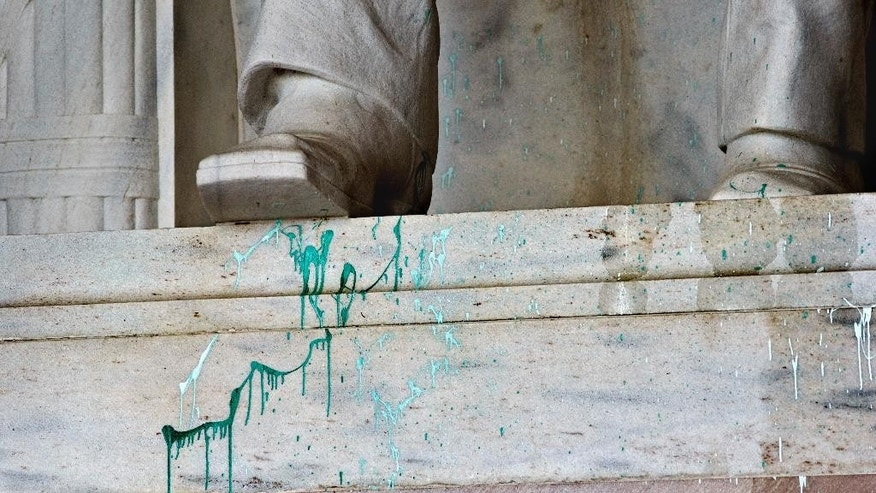 FILE - In this July 26, 2013 file photo, green paint splattered on the base of the statue of Abraham Lincoln at the Lincoln Memorial in Washington. A woman accused of splattering green paint at the Washington National Cathedral and suspected of committing similar vandalism at sites including the Lincoln Memorial in 2013 will not be prosecuted. Online court records show that a judge on Tuesday dismissed the case against Jiamei Tian, 60, who was arrested in July 2013 after being caught in the National Cathedral holding what appeared to be a soda can containing green paint.  (AP Photo/J. Scott Applewhite, File)