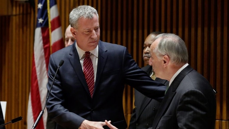 "New York Mayor Bill de Blasio, left, whales hands with  New York City Police Commissioner William Bratton as he introduces him at a news conference at New York City Police headquarters, Monday, Jan. 5, 2015. De Blasio says it was ""disrespectful"" that some NYPD officers turned their backs to him during a pair of funerals for slain police officers. (AP Photo/Richard Drew)"