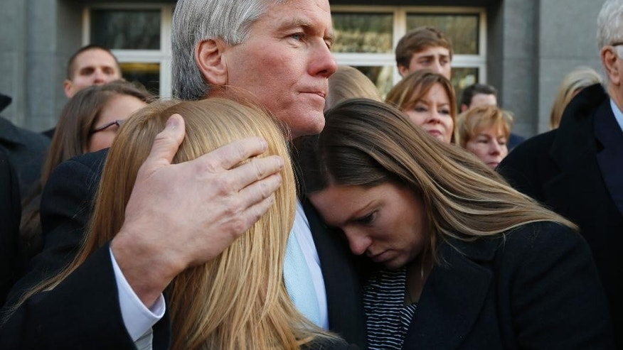 Former Virginia Gov. Bob McDonnell, center, hugs his daughters Cailin Young, left, and Jeanine McDonnell Zubowsky, right, after speaking outside federal court in Richmond, Va., Tuesday, Jan. 6, 2015.  McDonnell was sentenced to two years prison  and two years probation in his corruption case. He is to report to prison by Feb. 9. His wife, who was convicted on eight counts of corruption, will be sentenced Feb. 20.  (AP Photo/Steve Helber)