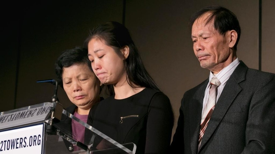 Pei Xia Chen, center, widow of slain New York City Police Officer Wenjian Liu, stands next to Liu's parents, Xiu Yan Li, left, and Wei Tang Liu, during a news conference at the Stephen Siller Tunnel to Towers Foundation, Wednesday, Jan. 7, 2015, in New York. The foundation says $860,000 has been donated and another $150,000 has been pledged to pay off the mortgages of Wenjian Liu and Detective Rafael Ramos, who were killed in December while on duty in Brooklyn. (AP Photo/Richard Drew)
