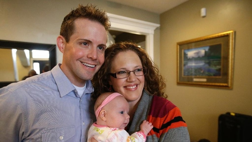 "Preston ""Pret"" and Megan Dahlgren hold their daughter Naomi as they pose for a photograph Monday, Jan. 5, 2015, near Salt Lake City. Two Utah men set to appear in the reality TV show ""My Husband's Not Gay,"" say they're fulfilled in their relationships to their wives even though they're attracted to other men. The show's concept has come under fire since it was announced by the TLC network last month.  (AP Photo/Rick Bowmer)"
