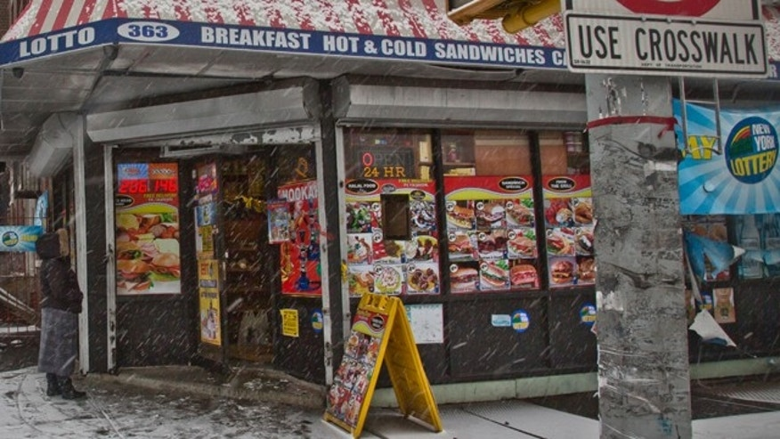 Jan. 6, 2015: A woman approaches a deli where a robbery occurred the night before in the Bronx borough of New York. Two New York City plainclothes police officers were shot while responding to the robbery late Monday. (AP Photo/Bebeto Matthews)