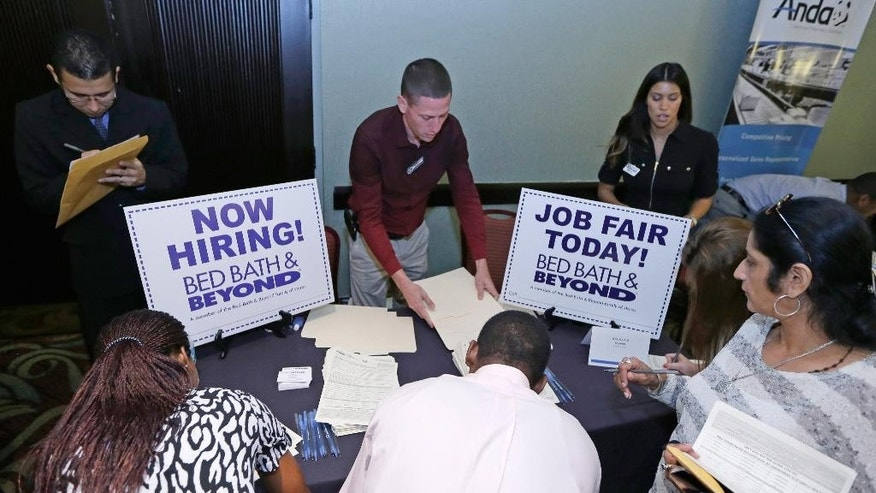 FILE - In this Oct. 22, 2014 file photo, job seekers fill out a job applications at a Bed Bath and Beyond table at a job fair in Miami Lakes, Fla.  The U.S. Labor Department reports on the number of people who applied for unemployment benefits for the week ending Jan. 3, 2015 on Thursday, Jan. 8, 2015. (AP Photo/Alan Diaz, File)