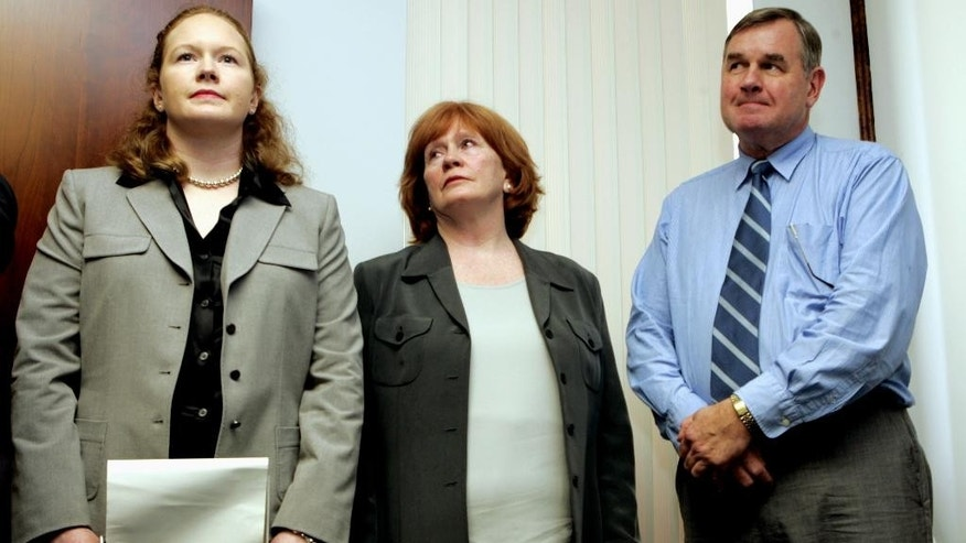 FILE - In this Dec. 9, 2005, file photo, Bree Smith, left, stands with her mother and father Maureen and George Smith while their attorney makes a statement during a news conference in Miami, regarding the disappearance of her brother and their son, George Smith IV. FBI officials have told relatives George Smith IV who disappeared during his honeymoon cruise in 2005 that they have ended their investigation of the case, the family's lawyer said Thursday, Jan. 8, 2015. (AP Photo/ Lynne Sladky, File)