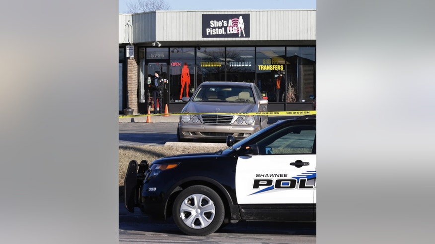 A law enforcement officer guards the scene of a shooting at She's a Pistol, LLC, in Shawnee, Kan., Friday, Jan. 9, 2015.  Emergency responders say three people were shot and wounded at the suburban Kansas City gun shop and a fourth person was wounded at a nearby location. (AP Photo/Orlin Wagner)