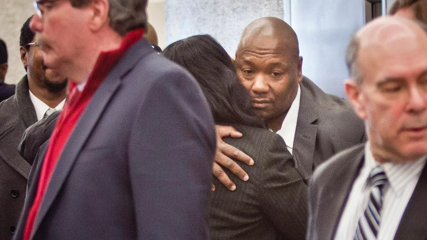 Derrick Hamilton, center, hugs his wife Nicole outside a courtroom after he was exonerated Friday, Jan. 9, 2015, in New York. Hamilton had served 21 years in prison before being paroled in 2011. The decision on Friday cleared his conviction. (AP Photo/Bebeto Matthews)