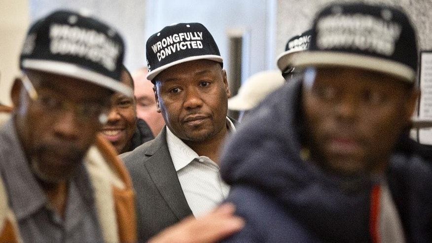 "Derrick Hamilton, center, walks among a group of men wearing caps reading ""wrongfully convicted,"" after he was exonerated on Friday, Jan. 9, 2015, in New York.  Hamilton's 1991 murder conviction was vacated after prosecutors told a New York City judge that the state's key witness had lied about who did it. The decision at the hearing cleared Hamilton, who had served 21 years in prison before being paroled in 2011. (AP Photo/Bebeto Matthews)"