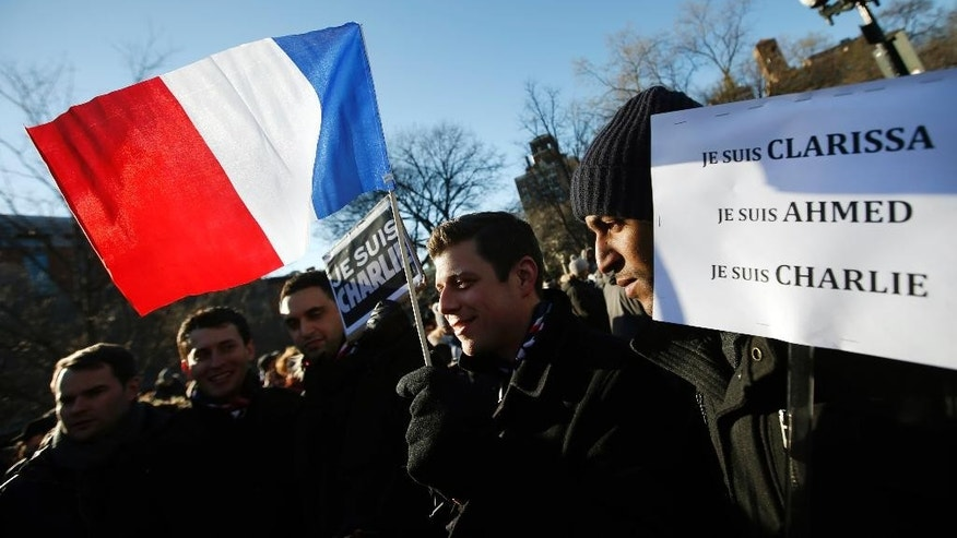 An attendee waves a French flag as several hundred people gather in solidarity with victims of two terrorist attacks in Paris, one at the office of weekly newspaper Charlie Hebdo and another at a kosher market, in New York's Washington Square Park, Saturday, Jan. 10, 2015. (AP Photo/Jason DeCrow)