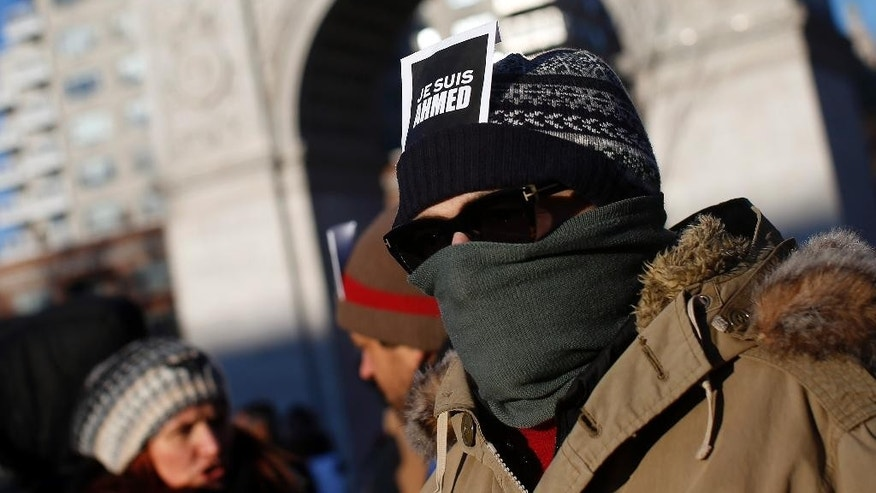 "An attendee wears a sign reading "" I am Ahmed"" as several hundred people gather in solidarity with victims of two terrorist attacks in Paris, one at the office of weekly newspaper Charlie Hebdo and another at a kosher market, in New York's Washington Square Park, Saturday, Jan. 10, 2015.  The sign refers to Muslim policeman Ahmed Merabet, who was shot dead outside the office of Charlie Hebdo. (AP Photo/Jason DeCrow)"