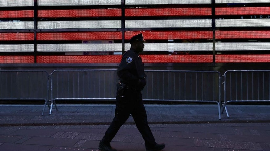 FILE. In this Jan. 8, 2015 file photo, a police officer walks through Times Squarein New York. In bustling Times Square, where scores of tourists wander through streets clogged with traffic and hawkers selling trinkets, low-level enforcement activity has all but grinded to a halt. The slowdown is happening city wide, but it's unclear whether it's a blip or the new status quo and what it means for the broken windows style of policing. (AP Photo/Seth Wenig, File)