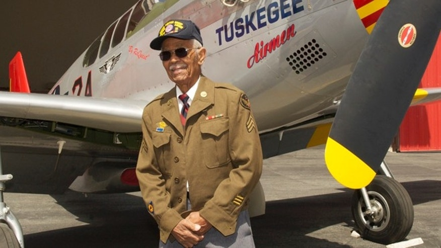 "This April 7, 2011 photo by Bruce Talamon shows Clarence E. ""Buddy"" Huntley Jr., a member of the Tuskegee Airmen, the famed all-black squadron that flew in World War II, posing with a P-51C Mustang fighter plane similar to the one that he was a crew chief on while overseas during the war, at Torrance, Calif., Airport."
