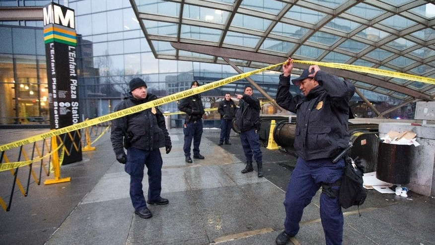Metro Transit Police officers secure the entrance to  L'Enfant Plaza Station in Washington, Monday, Jan. 12, 2015, following an evacuation. Metro officials say one of the busiest stations in downtown Washington has been evacuated because of smoke.  Authorities say the source of the smoke is unknown.  (AP Photo/Manuel Balce Ceneta)