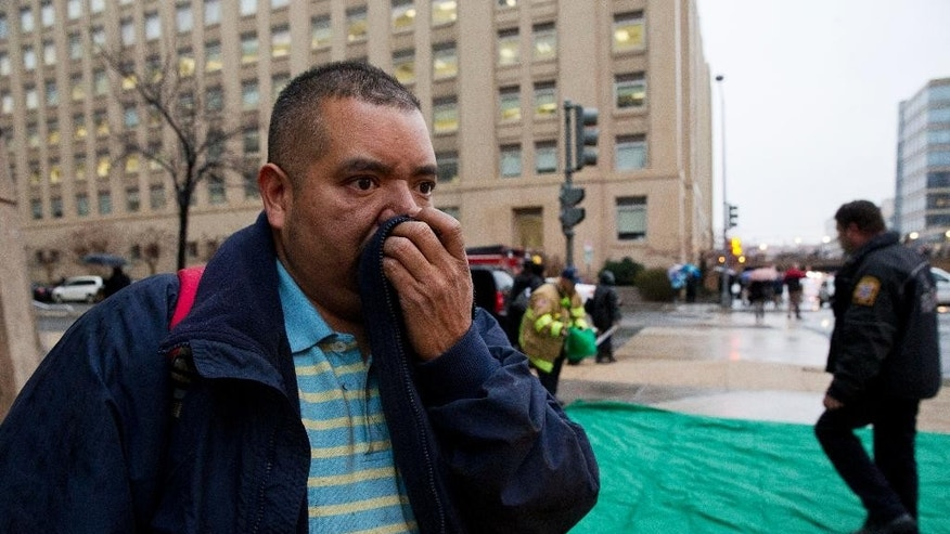 Reynaldo Hernandez holds a cloth over his smoke covered face as he coughs deeply after being evacuated from a smoke filled metro subway tunnel in Washington, Monday, Jan. 12, 2015.   Metro officials say one of the busiest stations in downtown Washington has been evacuated because of smoke.  Authorities say the source of the smoke is unknown.  (AP Photo/Jacquelyn Martin)