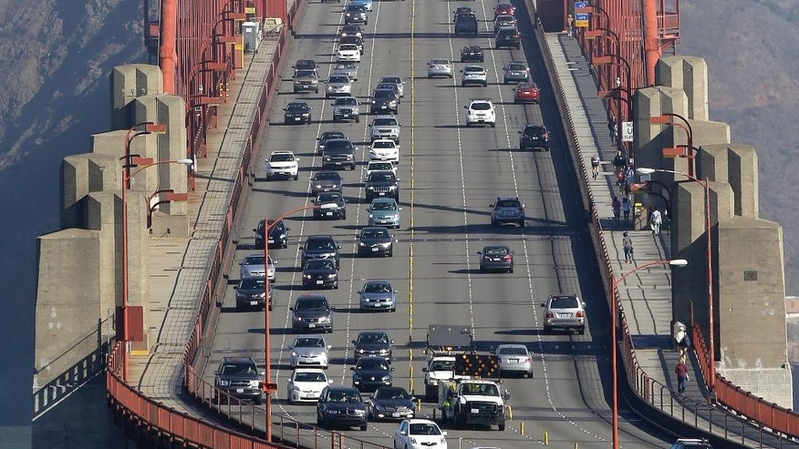 FILE - In this Thursday, Sept. 19, 2013 file photo, Golden Gate Bridge workers shift traffic lanes during the end of the morning commute in San Francisco. The Golden Gate Bridge will close to vehicles for 52 hours starting early Saturday morning, Jan. 10, 2014 to install a steel and concrete moveable median barrier that will help make the iconic bridge safer to commuters. (AP Photo/Eric Risberg)