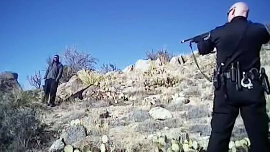 FILE - In this file photo taken from a video shot March 16, 2014, James Boyd, 38, left, is shown during a standoff with officers in the Sandia foothills in Albuquerque, N.M., before police fatally shot him. (AP/Albuquerque Police Department, File )