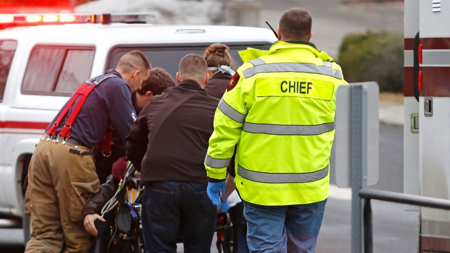Jan. 10, 2015: Emergency medical technicians rush one of two shooting victims to an ambulance after they were shot in an office in Moscow, Idaho