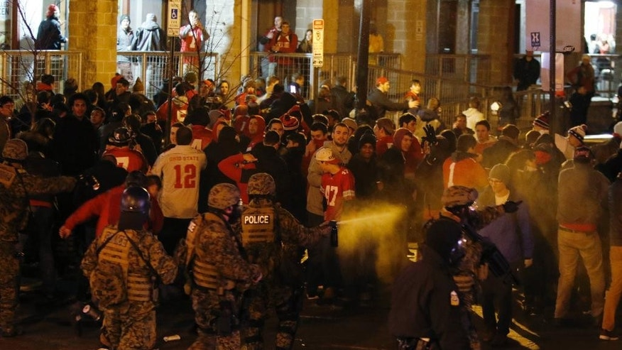 Police officers try to disperse the crowd of Ohio State fans trying to block High Street in Columbus, Ohio, as they celebrate the Buckeye's 42-20 win over Oregon following the National Championship football game between Ohio State and Oregon outside of Ohio State University in Columbus, Ohio, Monday, Jan. 12, 2015. (AP Photo/Paul Vernon)
