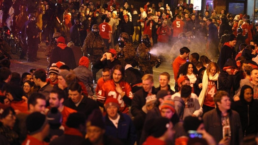 Police officers try to disperse the crowd of Ohio State fans blocking High Street in Columbus, Ohio, as they celebrate the Buckeye's 42-20 National Championship football game win over Oregon outside of campus Monday, Jan. 12, 2015. (AP Photo/Paul Vernon)