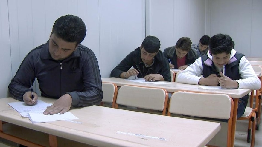 In this frame grab taken from video, 19-year-old Usame Isa, left, and other students take a test, Wednesday, Jan. 7, 2015, at a Syrian refugee camp in Turkey. Isa dreams of studying engineering, but he doesn't speak Turkish well enough to pass the language proficiency test required for entry at state universities. (AP Photo/Mehmet Guzel)