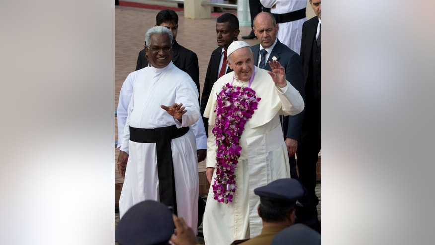 "Pope Francis, wearing a flower garland, waves to faithful as he arrives to Our Lady of Madhu shrine, in Madhu,  Sri Lanka, Wednesday, Jan. 14, 2015. Pope Francis traveled to the jungles of war-torn northern Sri Lanka on Wednesday to show solidarity with the victims of the country's 25-year civil war and urge forgiveness and reconciliation ""for all the evil which this land has known."" (AP Photo/Alessandra Tarantino, Pool)"