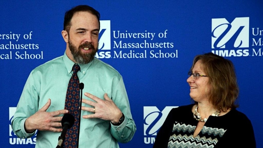 Dr. Rick Sacra talks about going back into the Ebola hot zone as his wife Debbie listens, Monday, Jan. 12, 2015, in Worcester, Mass. Sacra, who beat Ebola plans to return to Liberia, where he contracted the deadly virus, in order to help overworked colleagues in the missionary hospital where he has worked for years. (AP Photo/Worcester Telegram & Gazette, Chris Christo)
