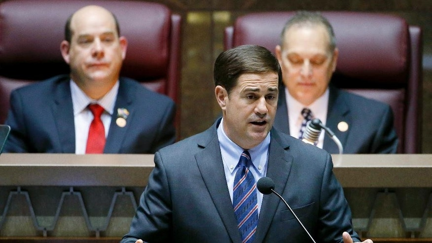 Arizona Republican Gov. Doug Ducey, front, gives his state-of-the-state address as Arizona House speaker David Gowan, left, R-Sierra Vista, and Arizona Senate President Andy Biggs, right, R-Gilbert, listen at the Arizona Capitol Monday, Jan. 12, 2015, in Phoenix. (AP Photo/Ross D. Franklin)