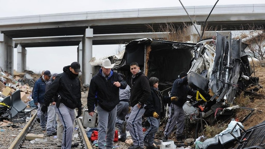 Officials investigate the scene of a prison transport bus crash, Wednesday, Jan. 14, 2015, in Penwell, Texas. Law enforcement officials said the bus carrying prisoners and corrections officers fell from an overpass in West Texas and crashed onto train tracks below, killing at least 10 people. (AP Photo/Odessa American, Mark Sterkel)
